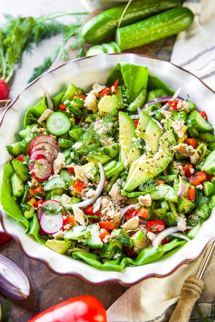 green lettuce, tuna, tomatoes, avocado, cucumber and radishes in a big salad bowl