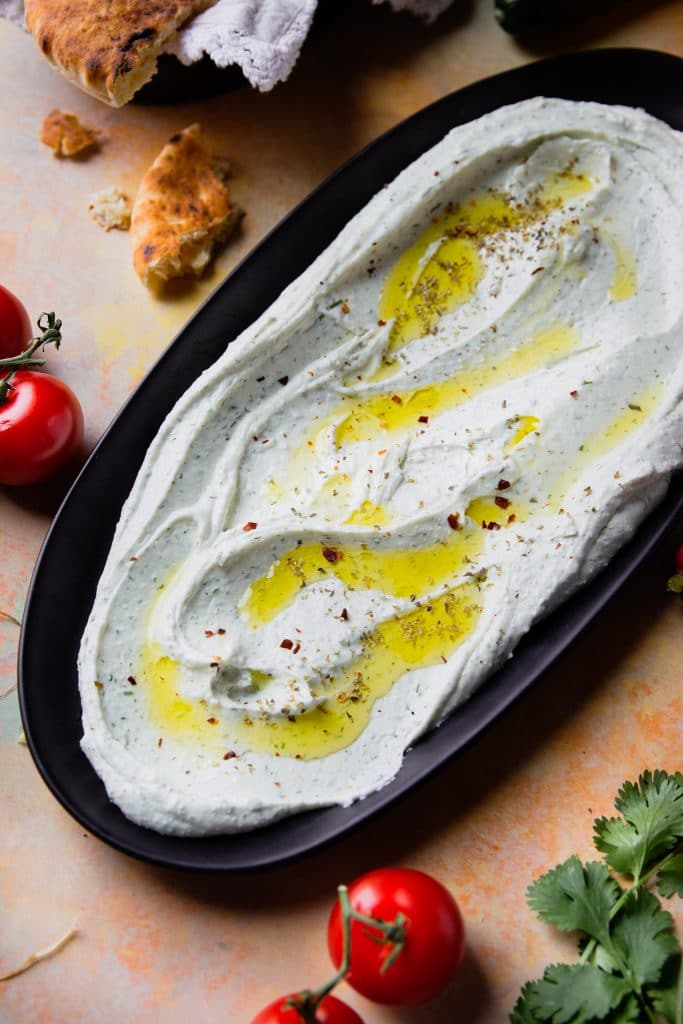 whipped feta dip spread on a black platter, topped with olive oil and herbs.