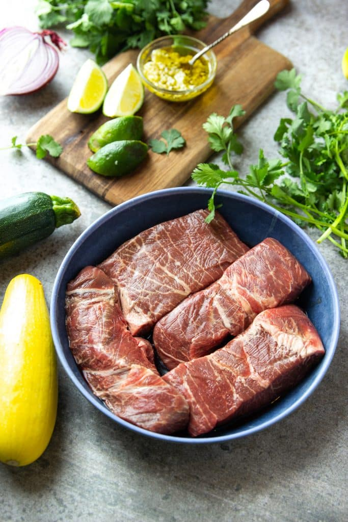 Four uncooked flat iron steaks in a blue bowl. Fresh cilantro, zucchini, summer squash and lime on the table.