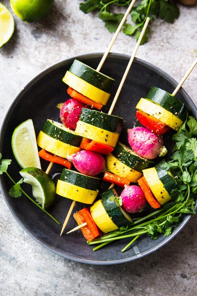 zucchini, summer squash, radish and red bell pepper in a kebab. Fresh cilantro and lime on a plate.
