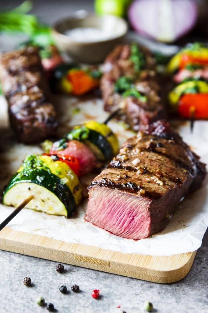 a sliced churrasco flat iron steak on a cutting board. A veggie kebabs grilled with cilantro chimichurri sauce.