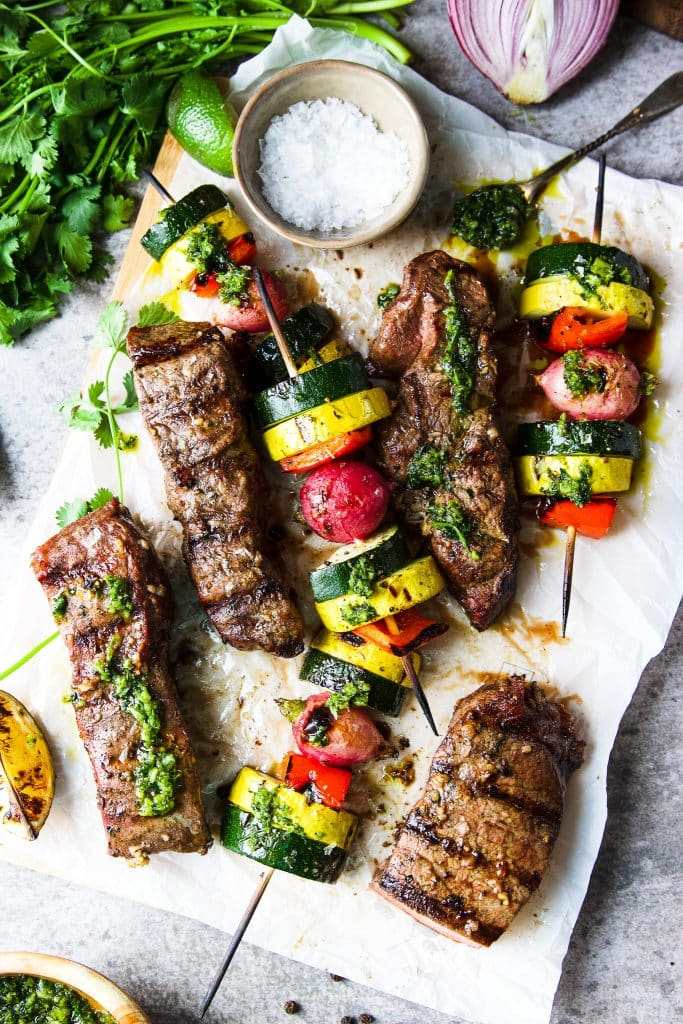 flat iron steaks on a cutting board with grilled veggies. A pinch bowl with sea salt and fresh herbs on the table.