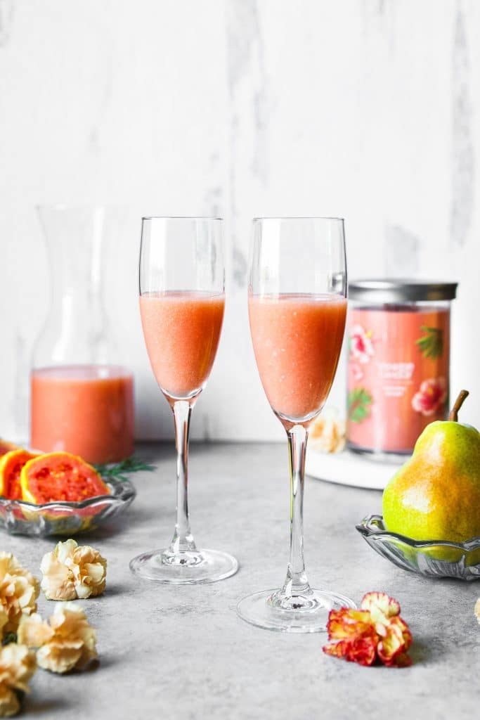 Two glasses of guava pear mimosa. Some guava and pears on a plate. Flowers scattered on the table. A candle and guava juice and the background
