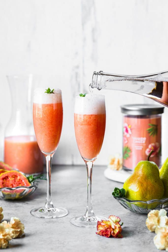 A hand pour sparkling rosé on to a champagne flute with guava juice.
