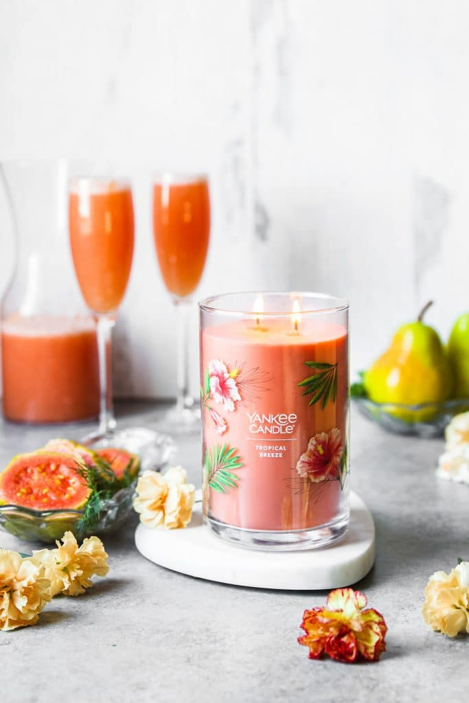 A candle burning on a white marble. Two glasses of guava pear mimosa in background. Some flowers scattered on the table and fruit on a plate.