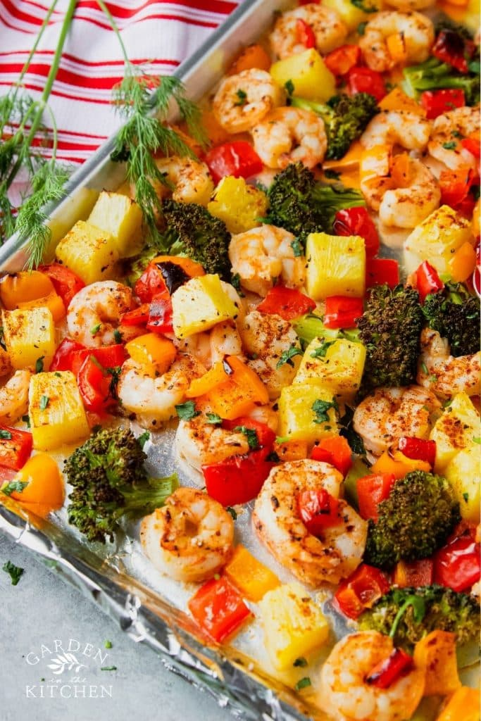 shrimp pineapple broccoli and bell peppers on a sheet pan
