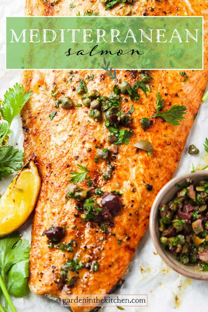 salmon on sheet pan with olives capers, a slice of lemon and fresh herbs