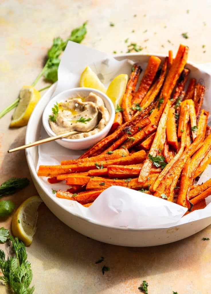 carrot fries served on a plate with sriracha mayo, garnished with parsley