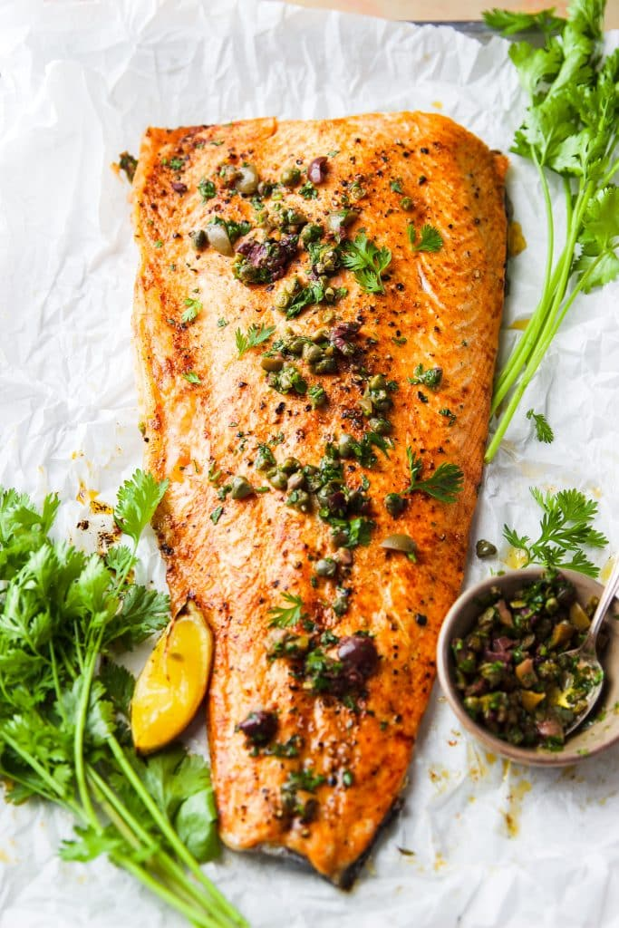 roasted salmon with mediterranean flavors such as olives, capers and fresh herbs