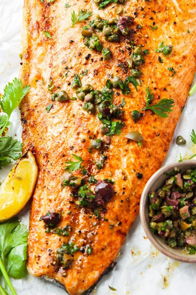salmon roasted in oven, topped with capers, olives and fresh herbs