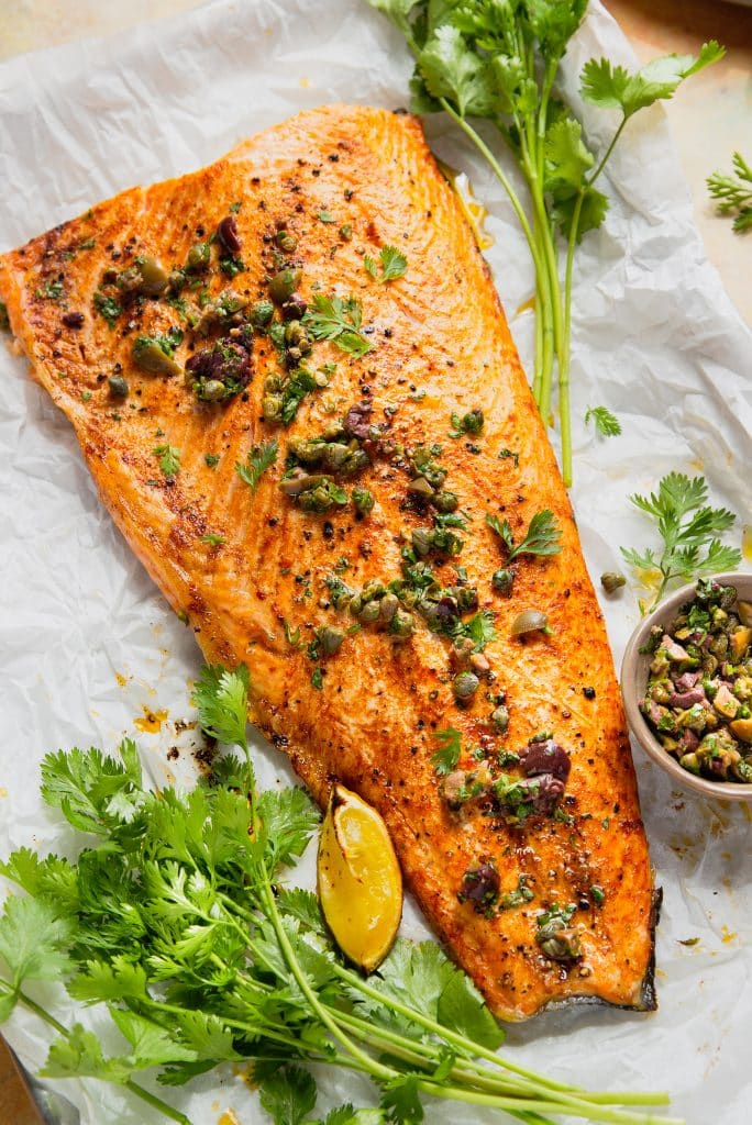salmon on a sheet pan, topped with capers and olives. fresh herbs on the side