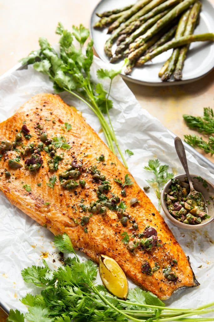 salmon on a sheet pan with fresh herbs, topped with olives and capers
