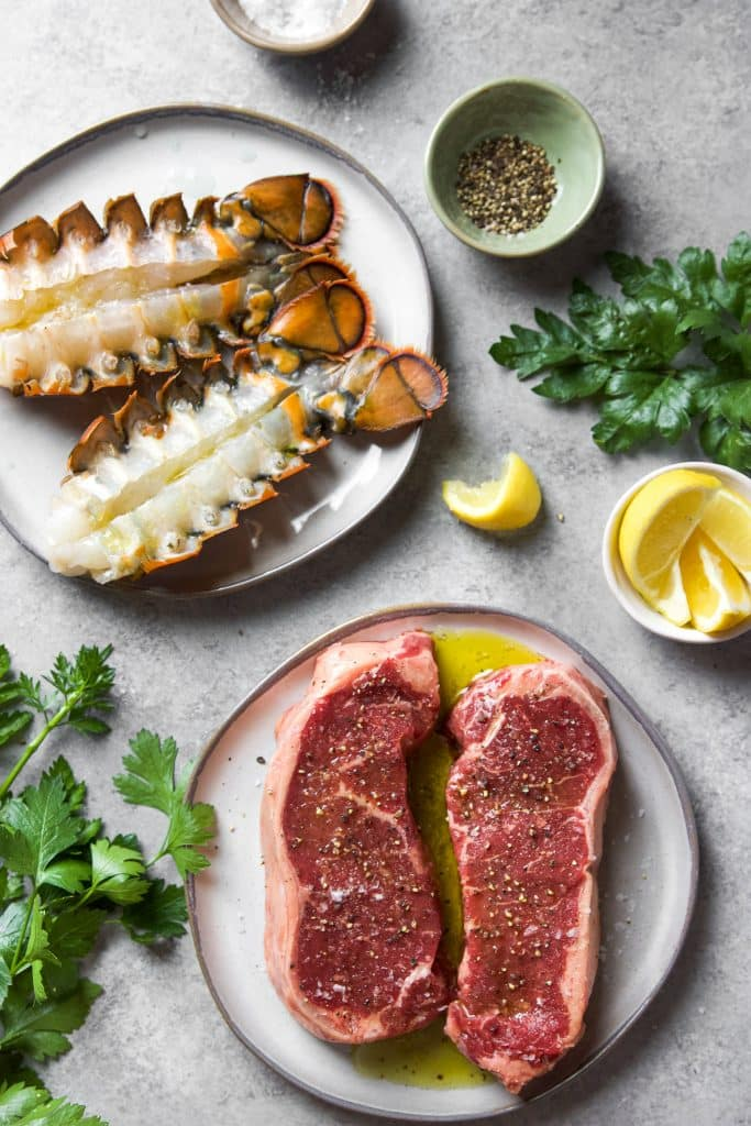 A plate with seasoned steaks. A second plate with two lobster tails. Some herbs and lemon slices on the table and a small bowl with ground pepper.