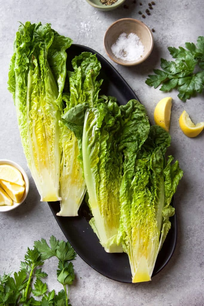 Romaine lettuce on a oval platter. A few slices of lemon on the table. A pinch bowl with salt and fresh herbs on the side.