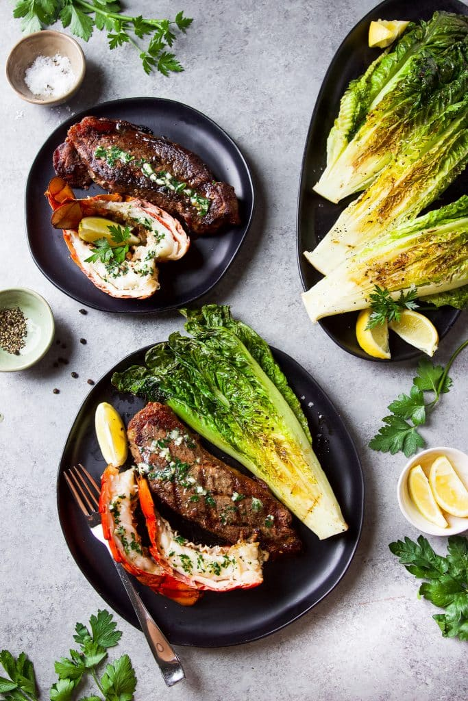 Two round black plates with a steak and lobster tail each. Grilled lettuce on a oval platter. Fresh herbs and lemon slices on the table.