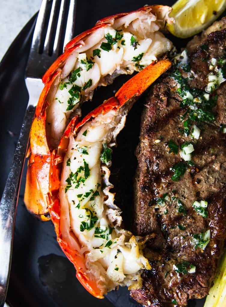 A close up look at a grilled steak and lobster tail on a plate.