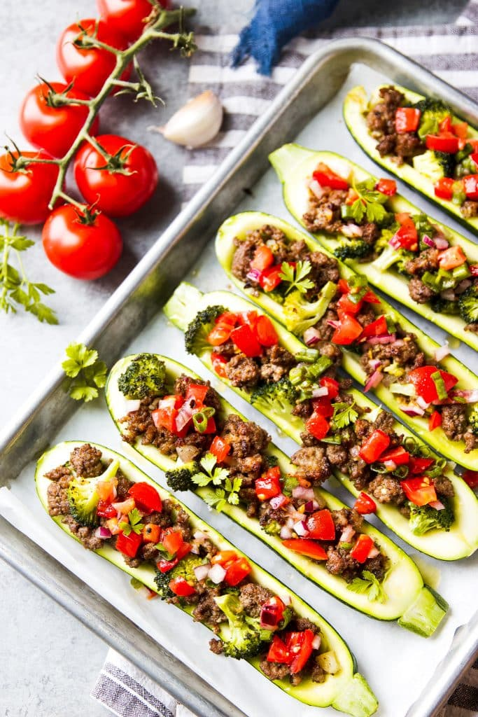 Stuffed zucchini boats with ground beef and broccoli topped with a homemade tomato salsa